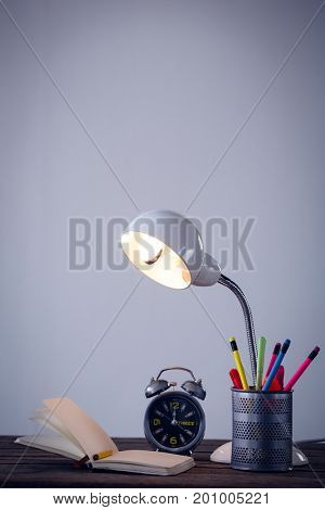 Illuminated electric lamp with desk organizer by book and alarm clock on table against wall
