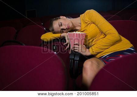 Young woman sleeping in a movie theatre