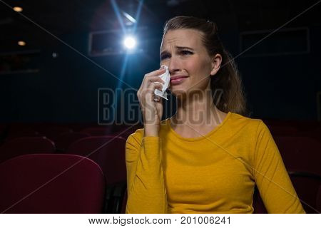 Woman crying while watching movie in theatre