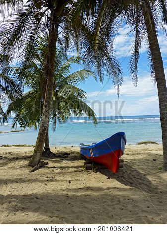 Boat on a tropical beach with coconut tree and the Caribbean sea in background Puerto Viejo de Talamanca Costa Rica Central America