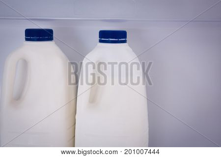 Close up of milk bottles with blue cap in refrigerator