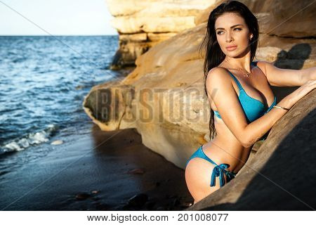 Sexy brunette girl in bikini posing on a beach