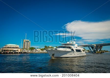 FORT LAUDERDALE, USA - JULY 11, 2017: Beautiful white yatch with a nice view behind of an opened draw bridge raised to let ship pass through at harbor in Fort Lauderdale, Florida.