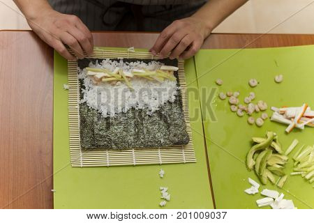 A person making sushi rolls with rice and a bamboo mat