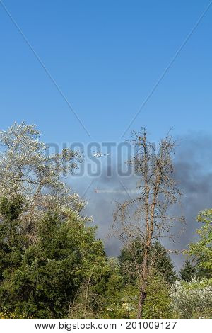 OLYMPIA, WASHINGTON, USA - AUGUST 22, 2017: UH-1 Huey helicopter drops water from red bucket to fight brush fire south of Olympia, Washington