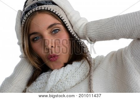 Close up portrait of young woman puckering while standing against white background