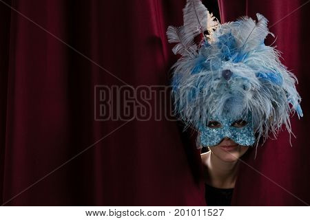 Smiling female artist in masquerade mask peeking through the red curtain