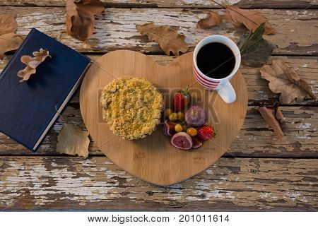 Overhead view of food with coffee cup on wooden tray by book at table