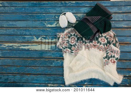 Directly above shot of warm clothes with gloves and ear muffs on wooden table