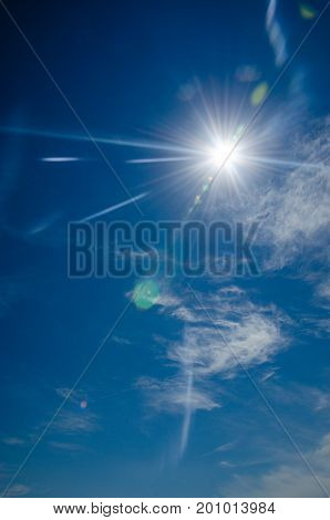 Sun with lens flare on blue sky background. Glare from the bright sun in a clear blue sky with a little cloudiness and the effect of vignetting