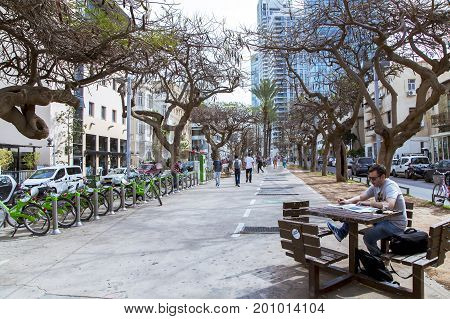 ISRAEL, TEL-AVIV, FEBRUARY, 23, 2016 - Quiet street in the center of new Tel Aviv. A man reads a newspaper at a table on a warm February morning in Tel-Aviv, Israel.