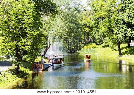 LATVIA, RIGA, JUNE, 20, 2015 - Pleasure boats cruise along the Riga river channel  in Riga central city park, capital of Latvia