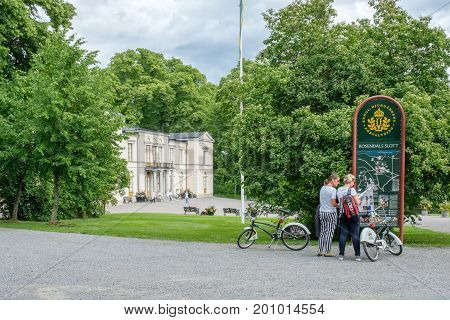 STOCKHOLM - JULY 5, 2017: Tourists with bikes at Rosendal palace in Stockholm. Rosendal palace located in the recreational area of Djurgarden is one of 11 Royal palaces in Sweden.