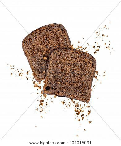 Sliced rye bread with crumbs frozen in the air on a white background