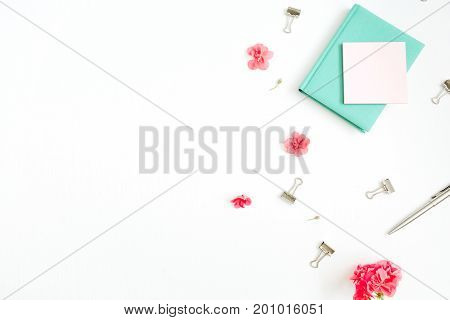 Flat lay fashion office desk. Female workspace with red flowers accessories mint diary on white background. Top view feminine background.