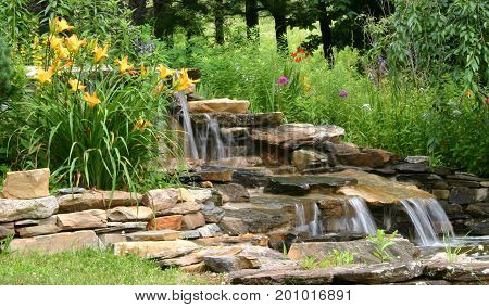 spring flowers surround a decorative waterfall fountain