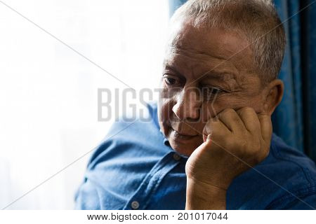 Close up of sad senior man with hand on chin sitting by window