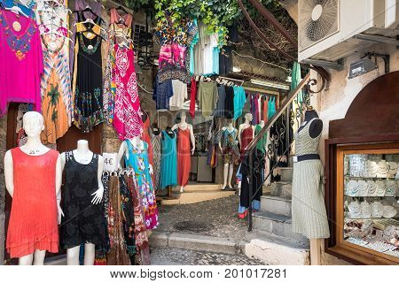 RHODES, GREECE - AUGUST 2017: Street shops with clothes in city of Rhodes on Rhodes island, Greece