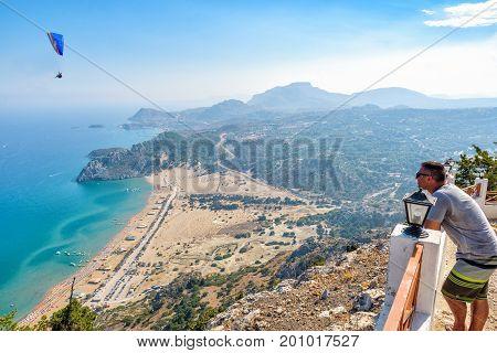 FALIRAKI, RHODES - AUGUST: Man is looking at Tsampika bay from balcony on Rhodes island, Greece