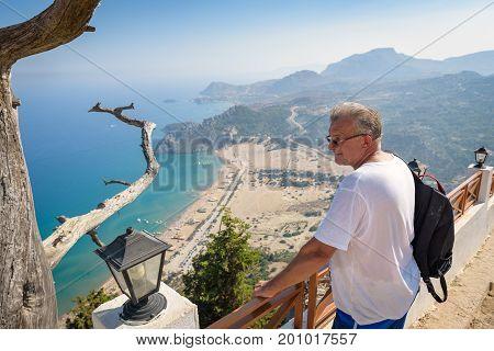 TSAMPIKA, RHODES - AUGUST 2017: Man is looking at Tsampika bay from balcony on Rhodes island, Greece