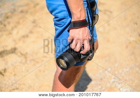 Dslr camera in the hands of a photographer on a sandy beach close up