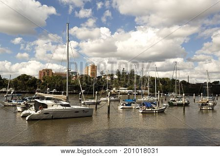 BRISBANE, AUSTRALIA - June 22, 2017: Yachts of all sorts and sizes moored on the Brisbane River at the heart of the city of Brisbane Australia