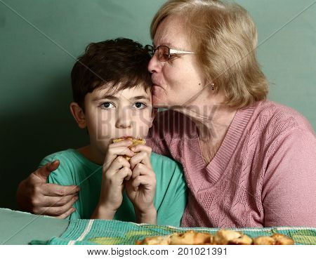 grannie with her grandson eating pie close up kiss photo