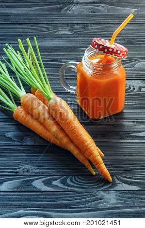 Healthy carrot smoothie in a jar with a red lid in a white polka dots and an orange straw and carrots on black wooden table . Healthy food background concept