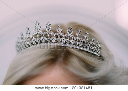Wedding diadem in a shape of crown on bride's head. Artwork. Close-up