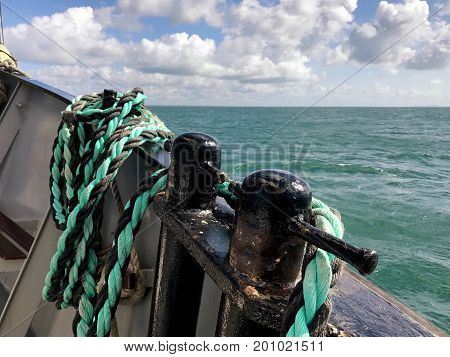 Ketch sailing at sea with a view of Samson posts and rope on the sides of the deck of the boat with the sea horizon and sky in the background. With space for text.
