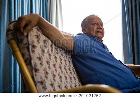 Side view of senior man looking away while relaxing on sofa at retirement home