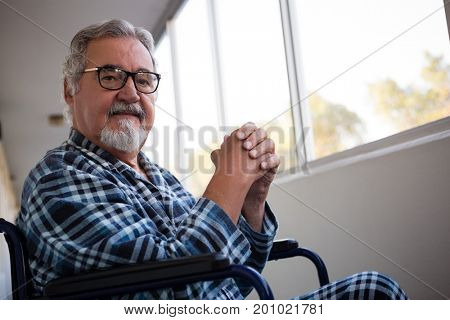 Portrait of senior man sitting on wheelchair by window in retirement home