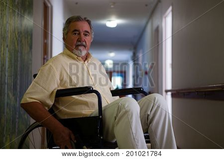 Portrait of senior man sitting on wheelchair in corridor at retirement home