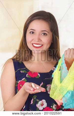 Close up of a smiling young woman, holding an assorted colorful underwears and a soft gelatin vaginal tablet or suppository, treatment of diseases of the reproductive organs of women and prevention of women's health.
