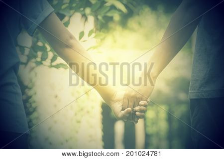 Romantic couple in love holding hands in the garden.