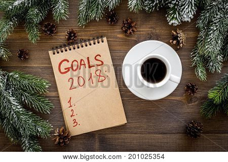 Goals list for 2018. Notebook near spruce branches and pine cones on wooden background top view.