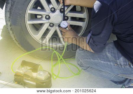 Auto mechanic uses a Car Tire Pressure Check in the Auto Service Garage. Selective focus.
