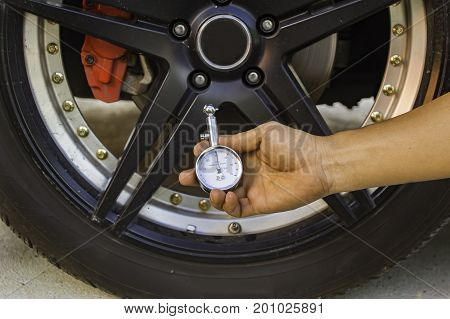 Auto mechanic Hand holding pressure gauge for car tyre pressure measurement Selective focus.