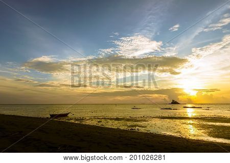 Coast of the sea at colorful sunset with fishing boat during low tide at Layangan Beach,Labuan island,Malaysia.