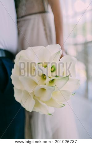 Beautiful Wedding Bouquet Of Calla Flowers In Hands Of The Bride. Artwork. Soft Focus On A Bouquet