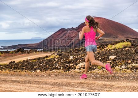 Trail runner athlete woman running training cardio on rocky mountain path on long distance endurance run in summer outdoors nature landscape. Female sports fitness person working out.