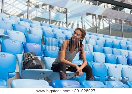Sexy Sport Girl Posing At Stadium With The Backpack. Fitness Girl With A Sports Figure In Black Legg