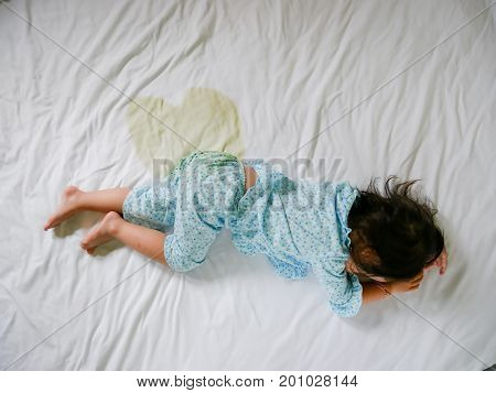 Bedwetting , Child pee on a mattress, Little girl feet and pee in bed sheet, Child development concept , selected focus at wet on the bed