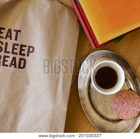 Brown paper bag suggesting a philosophy of eat, sleep and read with black coffee and biscuits.