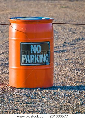 An orange barrel with suspended cable used to provide a warning and containment.