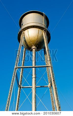 Low view of a tall water tower with bright blue sky background