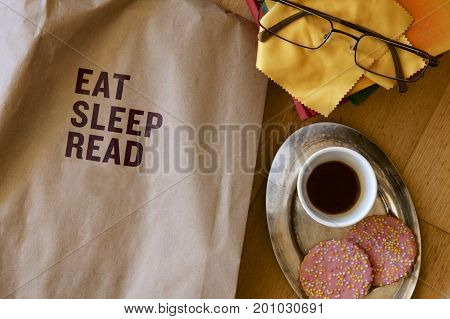 A suggestion to eat, sleep and read on a brown paper bag with coffee, biscuits and spectacles.