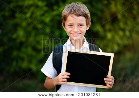 School kid holding a blackboard with back to school message