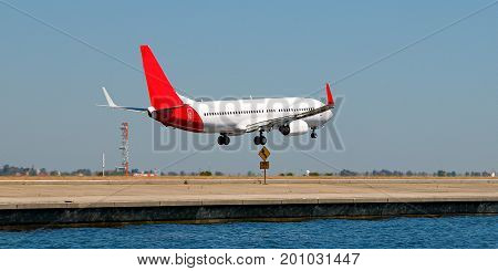 Commercial Jet Aircraft taking off in a sunny blue sky at Sir Kingsford Smith Airport Mascot Sydney Australia.