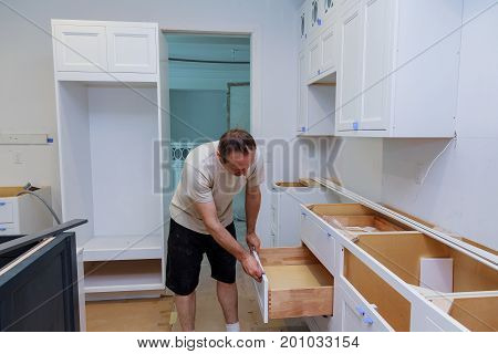 Installation Kitchen. Worker Installs Doors To Kitchen Cabinet.
